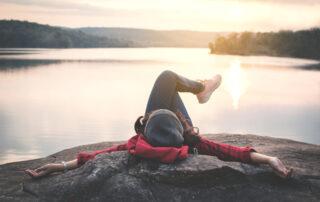 20-something female lying on rocks beside lake at sunrise