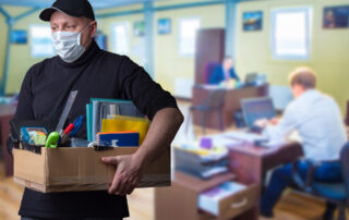 Man wearing facemask leaves office with his boxed possessions