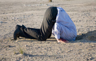 grown man on beach with head buried in the sand