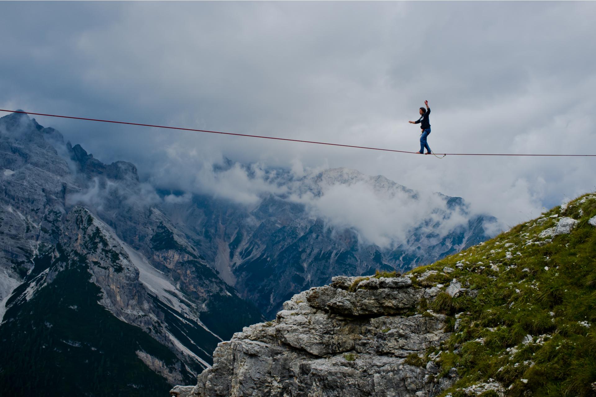 man walks tightrope between mountains