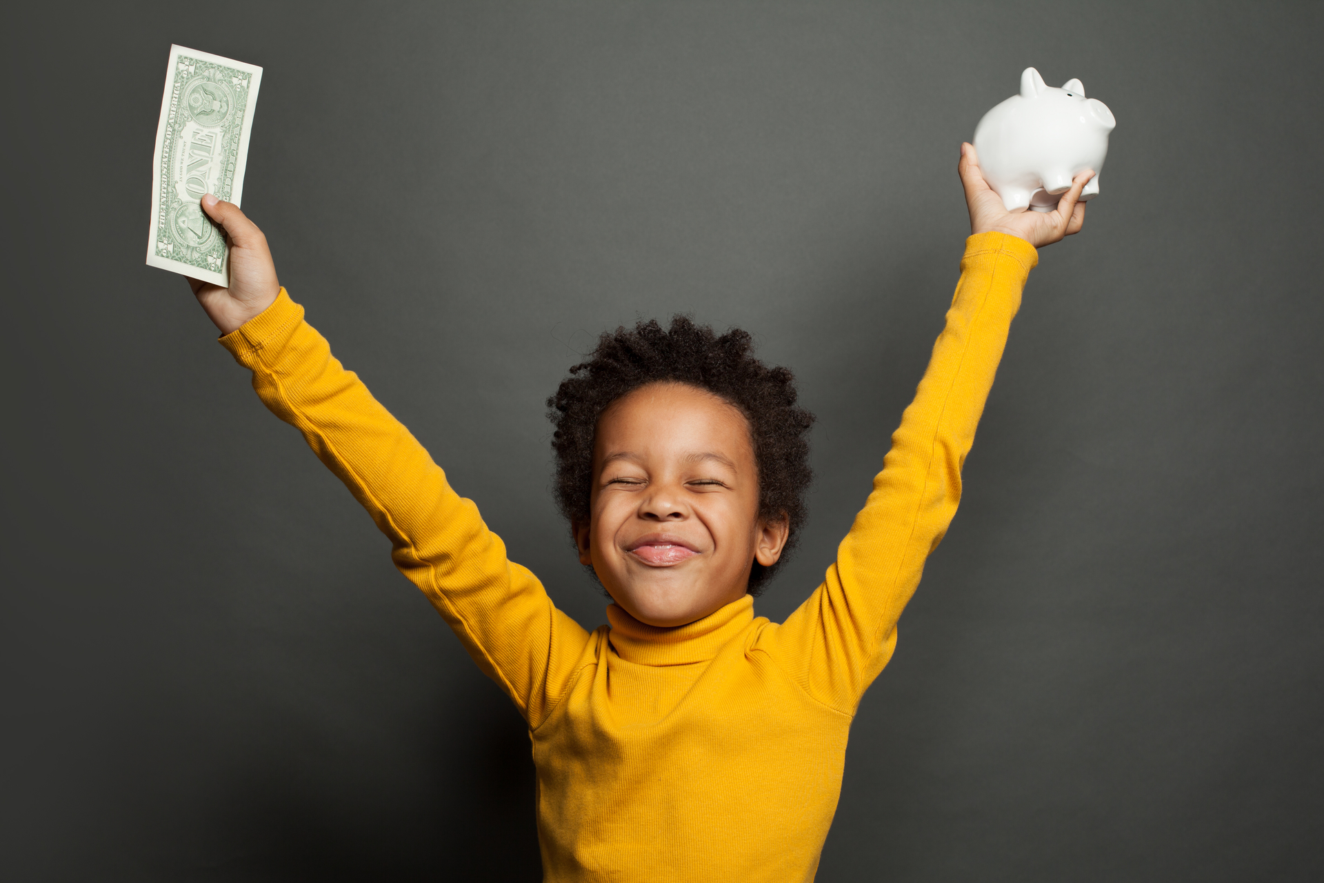 Young boy having fun with American dollars and a piggy bank