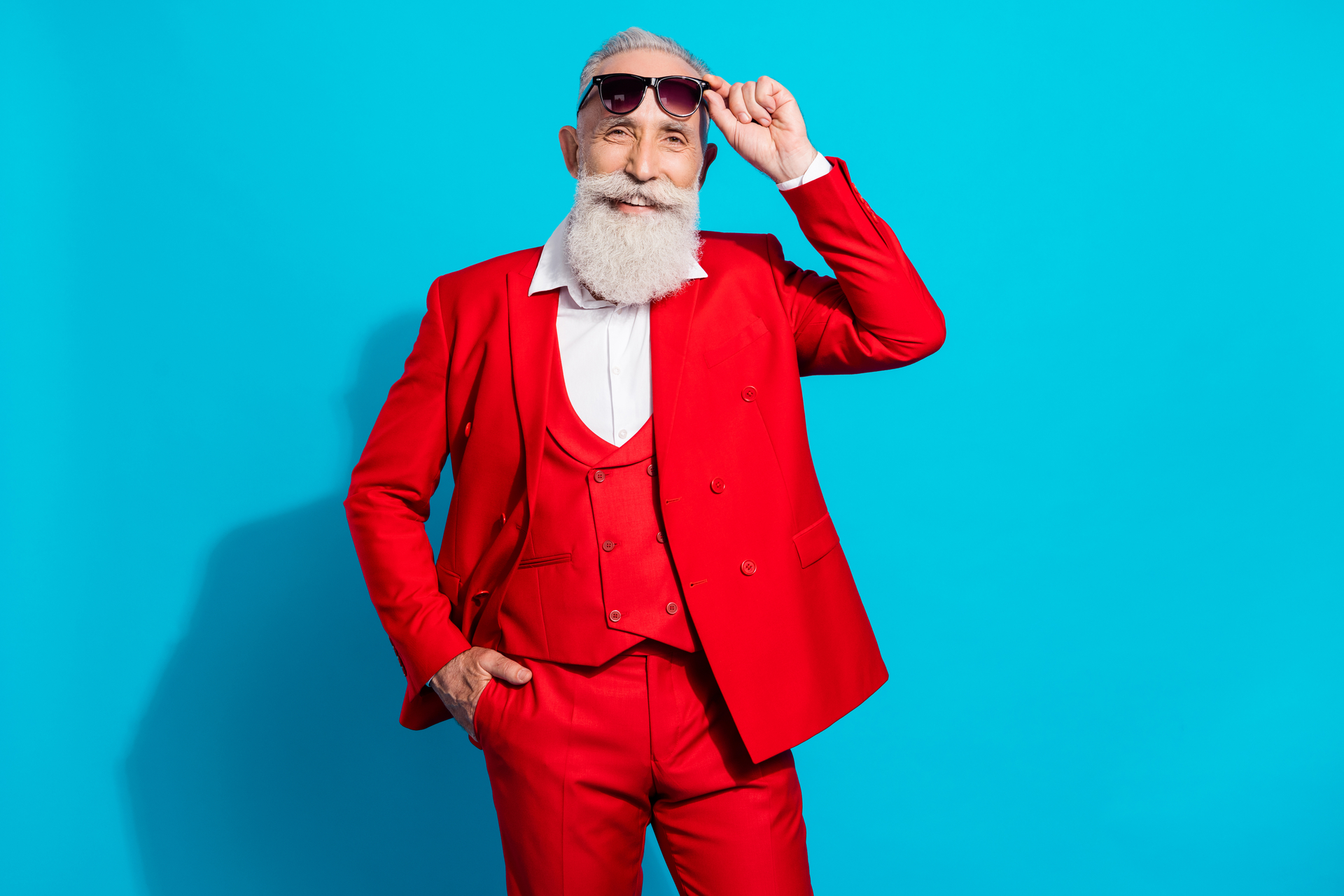 Smiling and stylish mature businessman with white beard wears sunglasses and red suit on bright blue background